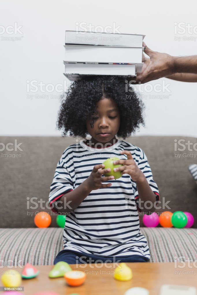 cute caucasian kid is play with book stack on head