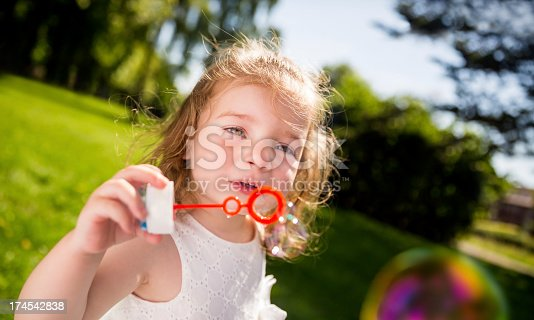 istock Cute caucasian little Girl Blowing Bubbles 174542838