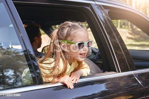 Blond caucasian child girl, wearing sunglasses and looking out the window while traveling with her parents in a car. Side view. Safe trip, journey driving concept.