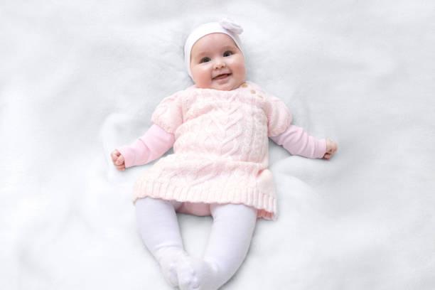 niedlich, fröhlich neugeborenen gekleidet in rosa hemdblusenkleid auf weißem fell decke. entzückende baby baby mit stirnband. - kleinkinder kleid häkeln stock-fotos und bilder