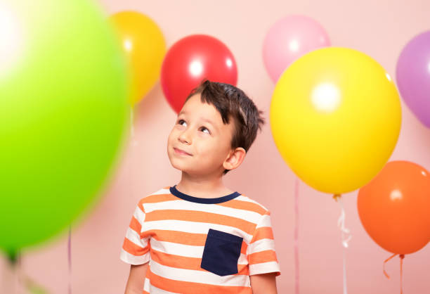 Cute child among colorful balloons. stock photo