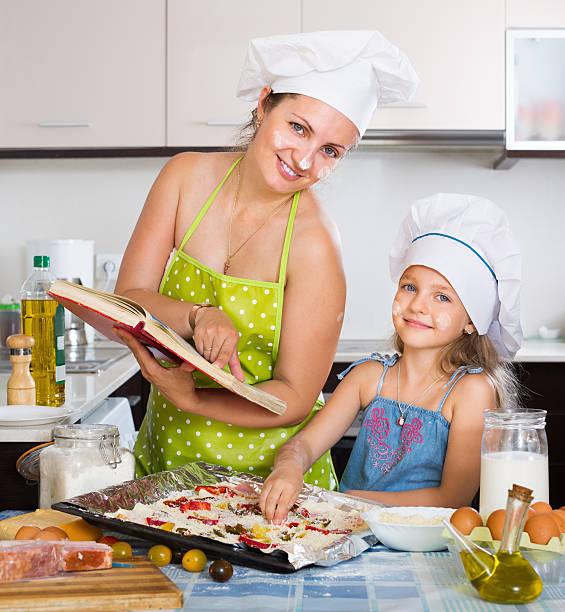 cute child and mother making a pizza - kids cooking stock photos and pictures