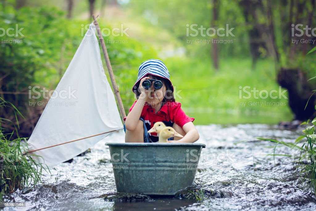 Cute child, boy, playing with boat and ducks on a little river, sailing and boathing. Kid having fun, childhood happiness concept stock photo