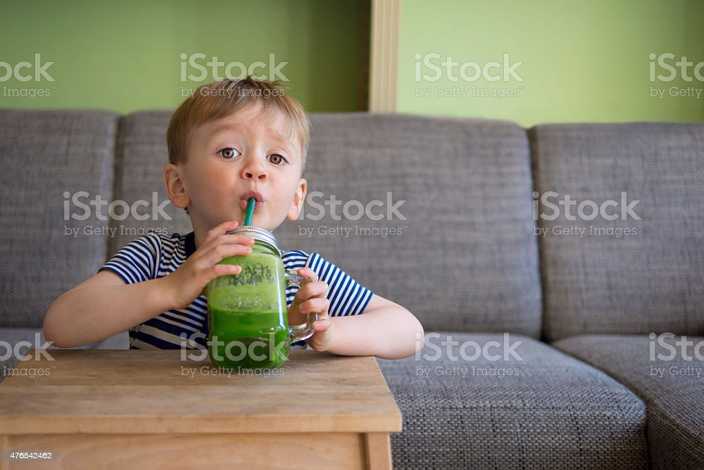 cute child drinking a green smoothie stock photo