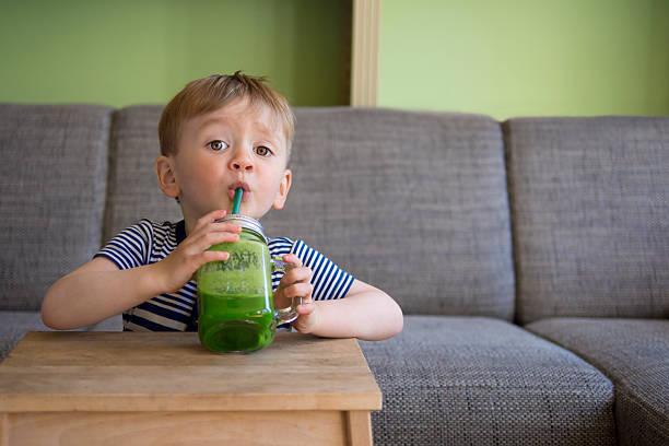 Niedliche Kind trinkt einen grünen smoothie – Foto