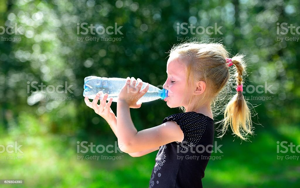 Cute child drinking water from a bottle стоковое фото