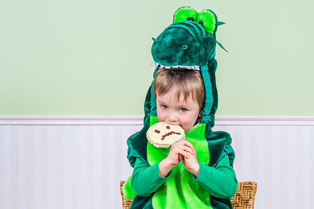 Cute child eating a Halloween cookie stock photo
