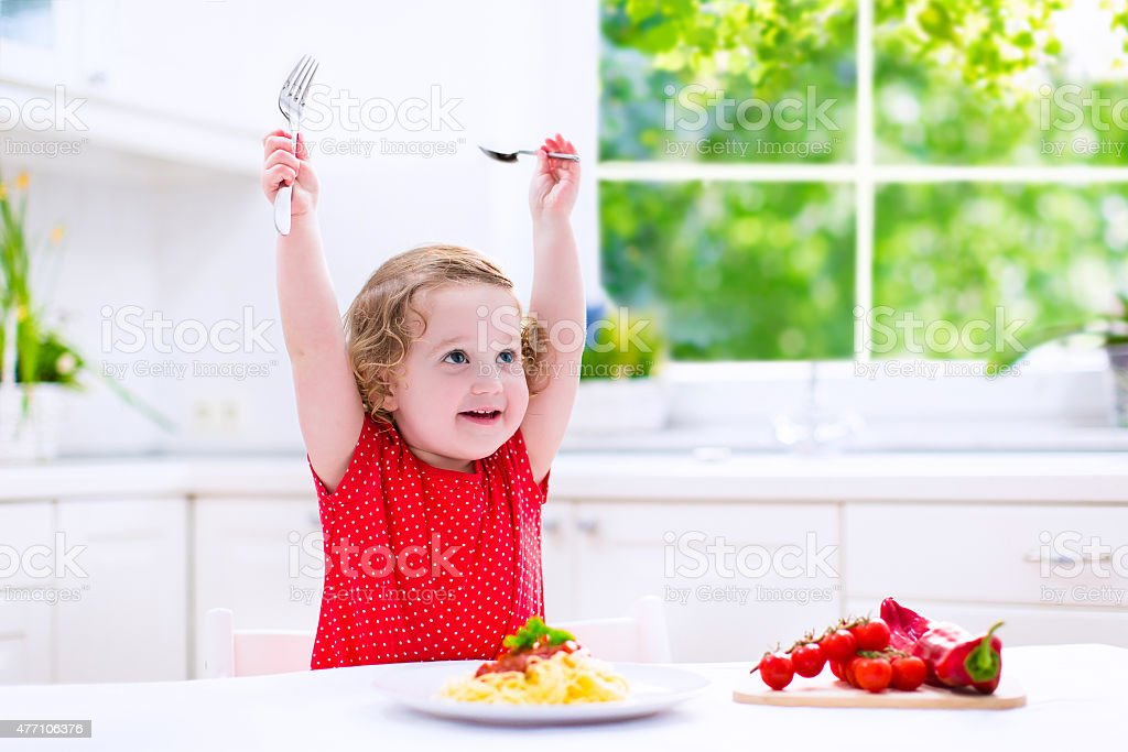 Cute child eating pasta Kids eat pasta. Healthy lunch for children. Toddler kid eating spaghetti Bolognese in a white kitchen at home. Preschooler child cooking noodles with tomato and pepper for dinner. Food for family. 2015 Stock Photo