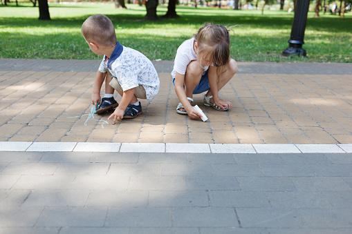 1019302738 istock photo Cute child girl and boy draws with chalk on the asphalt. Asphalt street art. Kids education. Childhood 1169360389