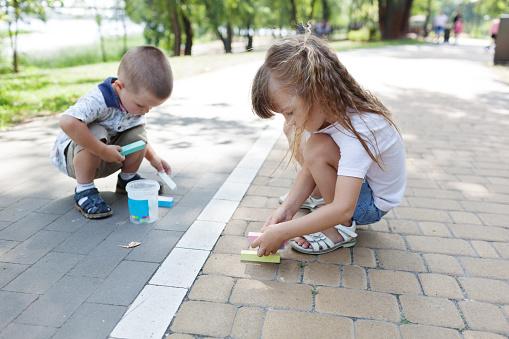 1019302738 istock photo Cute child girl and boy draws with chalk on the asphalt. Asphalt street art. Kids education. Childhood 1169376996