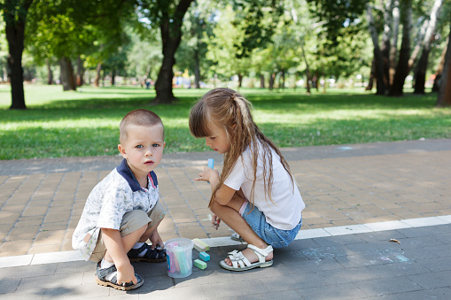 1019302738 istock photo Cute child girl and boy draws with chalk on the asphalt. Asphalt street art. Kids education. Childhood 1169377009