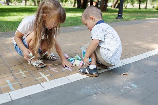 1019302738 istock photo Cute child girl and boy draws with chalk on the asphalt. Asphalt street art. Kids education. Childhood 1169377010