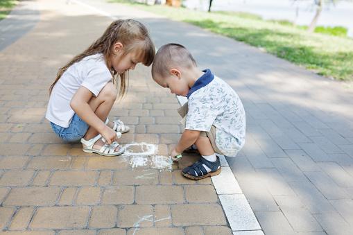1019302738 istock photo Cute child girl and boy draws with chalk on the asphalt. Asphalt street art. Kids education. Childhood 1169377011