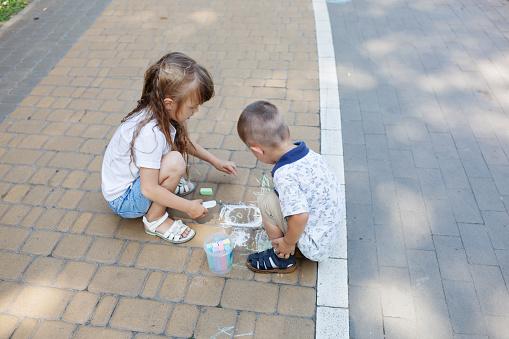 1019302738 istock photo Cute child girl and boy draws with chalk on the asphalt. Asphalt street art. Kids education. Childhood 1169377015