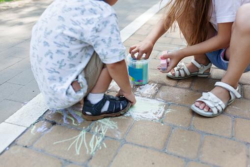 1019302738 istock photo Cute child girl and boy draws with chalk on the asphalt. Asphalt street art. Kids education. Childhood 1169377059
