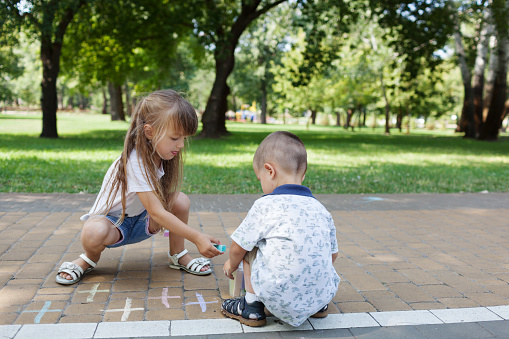 1019302738 istock photo Cute child girl and boy draws with chalk on the asphalt. Asphalt street art. Kids education. Childhood 1169377062