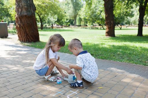 1019302738 istock photo Cute child girl and boy draws with chalk on the asphalt. Asphalt street art. Kids education. Childhood 1170672889
