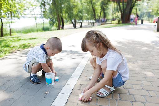 1019302738 istock photo Cute child girl and boy draws with chalk on the asphalt. Asphalt street art. Kids education. Childhood 1170672909