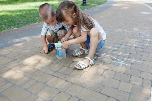 1019302738 istock photo Cute child girl and boy draws with chalk on the asphalt. Asphalt street art. Kids education. Childhood 1170672925