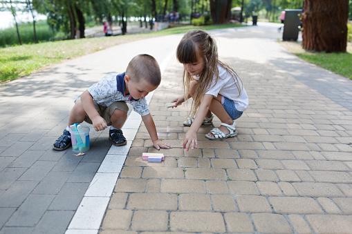 1019302738 istock photo Cute child girl and boy draws with chalk on the asphalt. Asphalt street art. Kids education. Childhood 1173111084