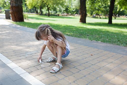 1019302738 istock photo Cute child girl draws with chalk on the asphalt. Asphalt street art. Kids education. Childhood 1170673465