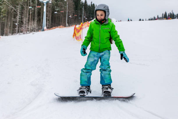 Cute child girl is snowboarding on the snow mountain stock photo