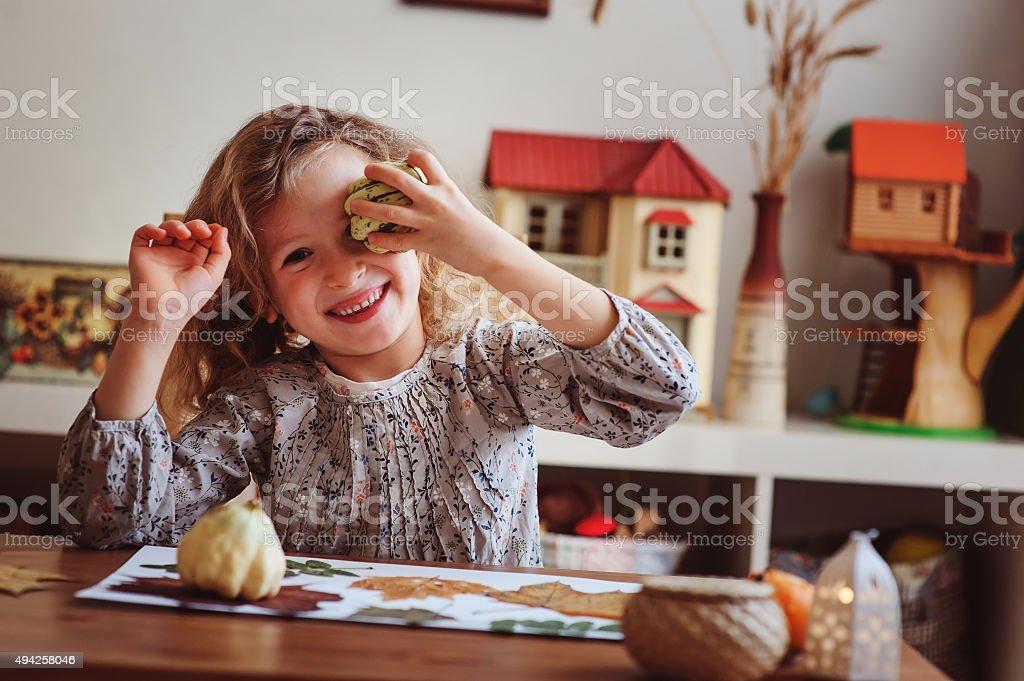 cute child girl making herbarium at home, autumn seasonal crafts stock photo