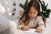 Cute smiling child girl writing letter to Santa Claus at home