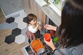 おしゃぶりを与えるかわいい子供は、おしゃぶりを母親に洗う