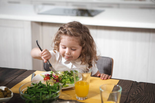 Cute child having tasty lunch at home stock photo