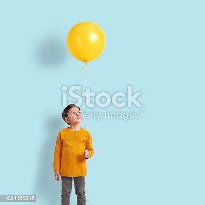 istock Cute child holding a yellow balloon 1084158318