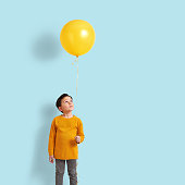 6-7 years old child holding a yellow balloon in front of blue wall.