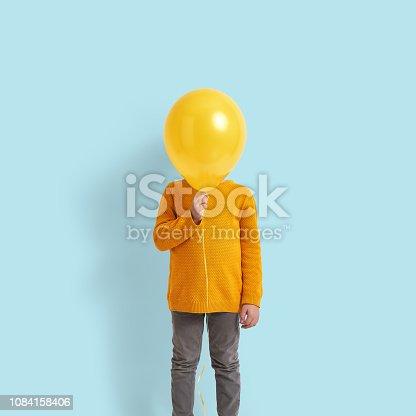 istock Cute child holding a yellow balloon 1084158406