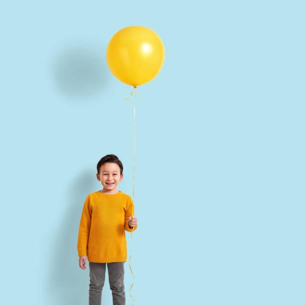 niedlichen kind hält einen gelben ballon - schulkind nur jungen stock-fotos und bilder