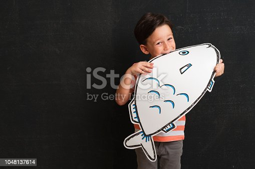 Cute child is holding fish drawing on dark background. Child is 5-6 years old.