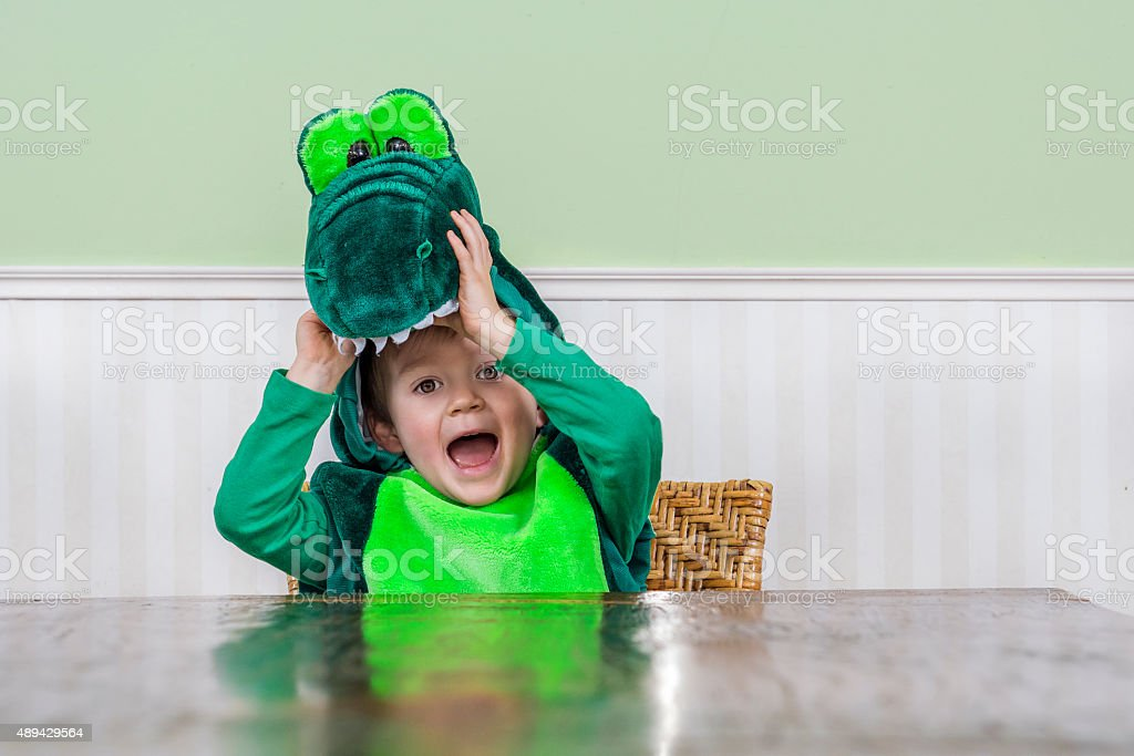 Cute child in crocodile suit stock photo