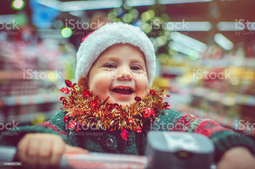 Cute child in shopping cart in Christmas stock photo