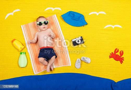 Cute child in swimming trunks is lying on a towel. Nearby are UV sunscreen, panama hat, glasses, crab, sandals and camera crab. Dreams of sea, adventures and travel. Summer vacation and travel concept