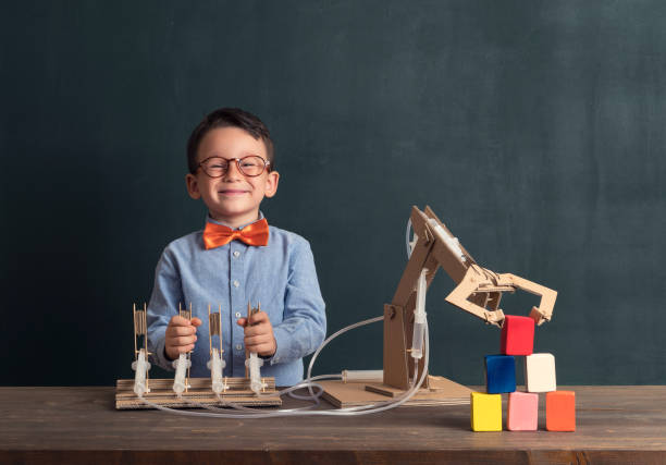 Cute child invented robot arm with cardboard. The child invented a robotic arm. He used cardboard and syringe. This is an innovation for her. He is a successful student at the age of 4-5. Robotic is technology of future. one boy only stock pictures, royalty-free photos & images