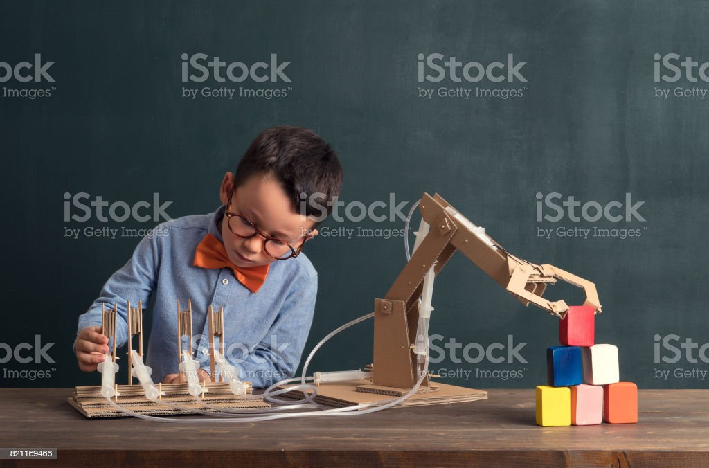 Cute child invented robot arm with cardboard. stock photo