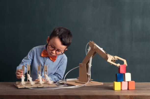 Nettes Kind erfunden Roboterarm mit Karton. – Foto