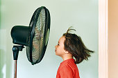 istock Cute child is front of electric fan on hot summer day 1253037864
