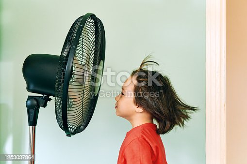 Cute child is front of electric fan on hot summer day