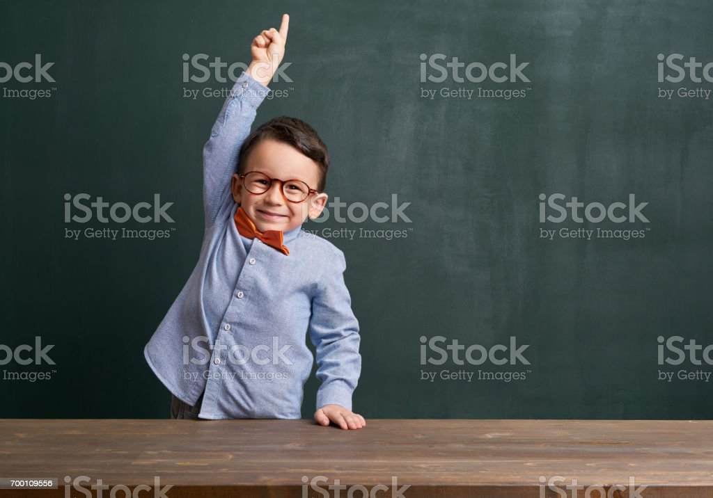 Cute child is in front of chalkboard and raising hand