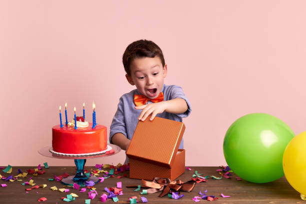 cute child is opening his gift - birthday gift stock photos and pictures