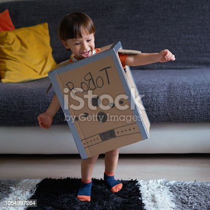 2-3 years cute child is wearing cardboard robot costume at home