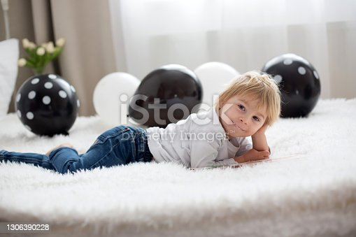istock Cute child, lying in bed, reading book 1306390228
