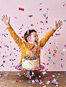 istock Cute child on pink background with cake and party confetti. Birthday party and big celebration. 1204656827
