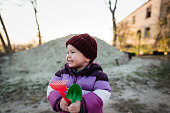 Portrait of cute child who holds a toys for playing in a sand on spring or autumn