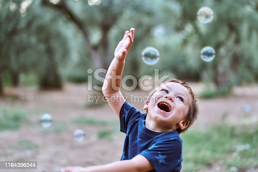 Cute child playing with bubbles